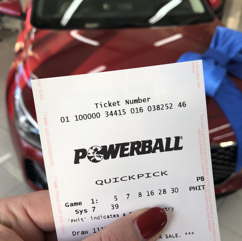 Powerball ticket held up in front of new car.