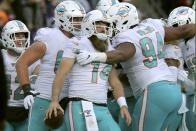 Miami Dolphins quarterback Ryan Fitzpatrick, center, celebrates his touchdown run with teammates in the second half of an NFL football game against the New England Patriots, Sunday, Dec. 29, 2019, in Foxborough, Mass. (AP Photo/Charles Krupa)
