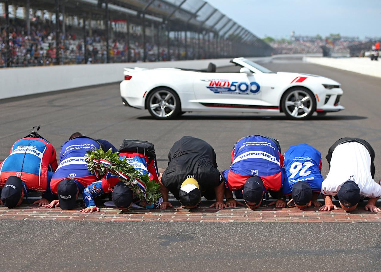 May 28, 2017; Indianapolis, IN, USA; IndyCar Series driver Takuma Sato and crew kiss the bricks as he celebrates after winning the 101st Running of the Indianapolis 500 at Indianapolis Motor Speedway. Mandatory Credit: Mark J. Rebilas-USA TODAY Sports     TPX IMAGES OF THE DAY
