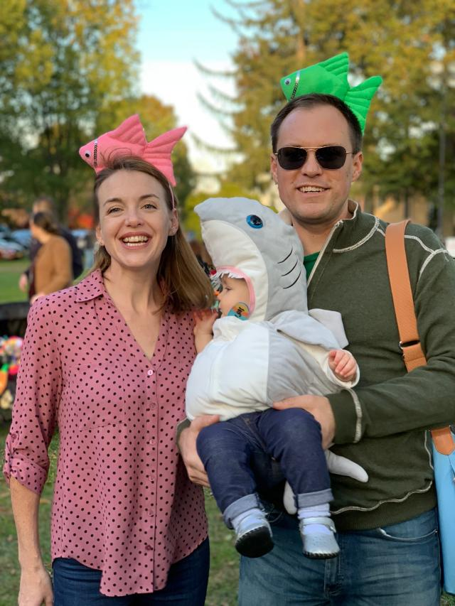 """This image released by Jason Simms shows him with his wife Jillian and their daughter Fionnuala wearing a shark costume on the Town Green in Madison, Conn. Fionnuala first heard the """"Baby Shark"""" song when she was 8 months old. Her parents say it was one of the first things in life she directly expressed a preference for, so they picked it for her Halloween costume. (Jason Simms via AP)"""