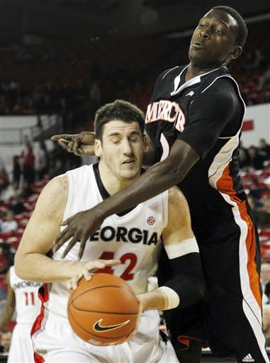 Georgia forward Nemanja Djurisic (42) goes up for a shot as Mercer guard Travis Smith (2) defends in the first half of an NCAA college basketball game in Athens , Ga., Tuesday, Dec. 20, 2011. (AP Photo/John Bazemore)