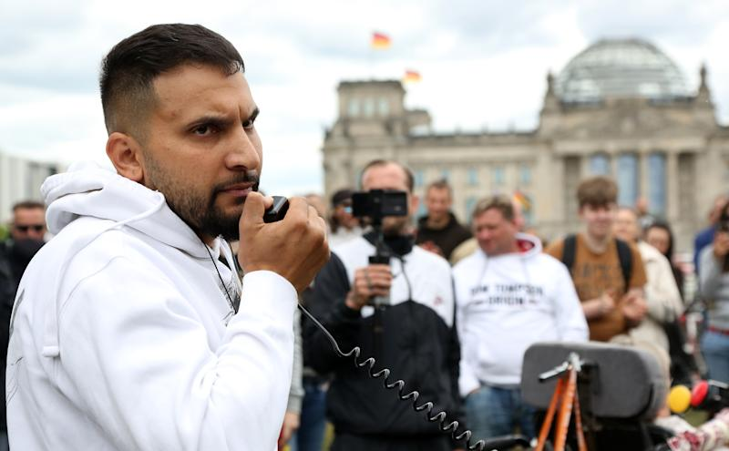 BERLIN, GERMANY - MAY 30: German vegan cookbook author and activist Attila Hildmann speaks as demonstrators attend a protest rally against coronavirus restrictions next to the German federal Chancellery, in front of the Reichstag, seat of the German federal parliament, during the novel coronavirus crisis on May 30, 2020 in Berlin, Germany. Similar demonstrations have been held across the country for weeks, drawing people from a wide political spectrum who feel government-imposed restrictions to stem the spread of the virus are undemocratic and too invasive, even as many of the preventative measures are lifted. (Photo by Adam Berry/Getty Images)