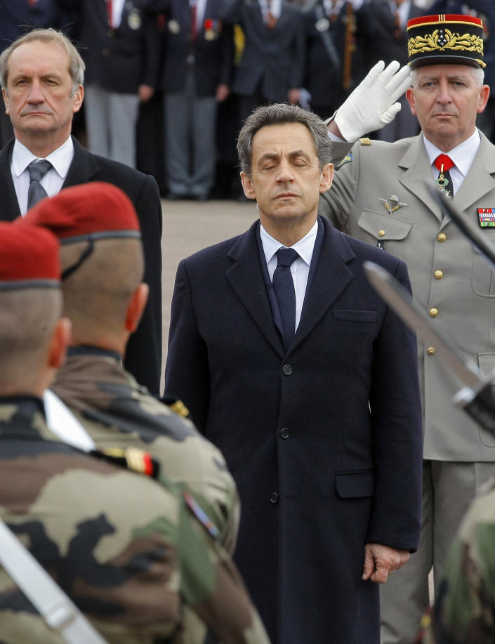 French President Nicolas Sarkozy, center, and Defense Minster Gerard Longuet, left, pay homage to the three soldiers killed by a suspect Interior Ministry official identified as Mohammad Merah, claiming al-Qaida links, and also suspected in the killings of three Jewish children and a rabbi, Wednesday, March 21, 2012 in Montauban, southwestern France. Soldliers were Imad Ibn-Ziaten, 30, a paratrooper in the 1st Airborne Transportation Regiment based in Toulouse, Abel Chennouf, 25, who served in the 17th paratrooper combat engineering regiment based in Montauban and Mohamed Legouade, 26, the second paratrooper killed in the same shooting. (AP Photo/Jacques Brinon, Pool)