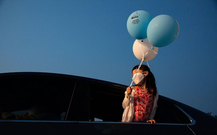 A little girl watches a drive-in music concert in Seoul on 17 July - Shutterstock