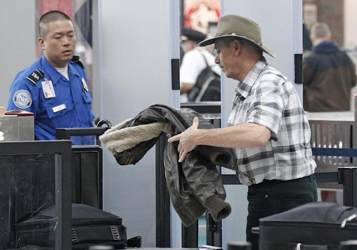 This April 30, 2012, photo shows a traveler passing through a security check point at Portland International Airport, in Portland, Ore. Airport security procedures, with their intrusive pat downs and body scans, don't need to be toughened despite the discovery of a new al-Qaida airline bomb plot using more sophisticated technology than an earlier attempt, congressional and security officials said Tuesday. (AP Photo/Rick Bowmer)
