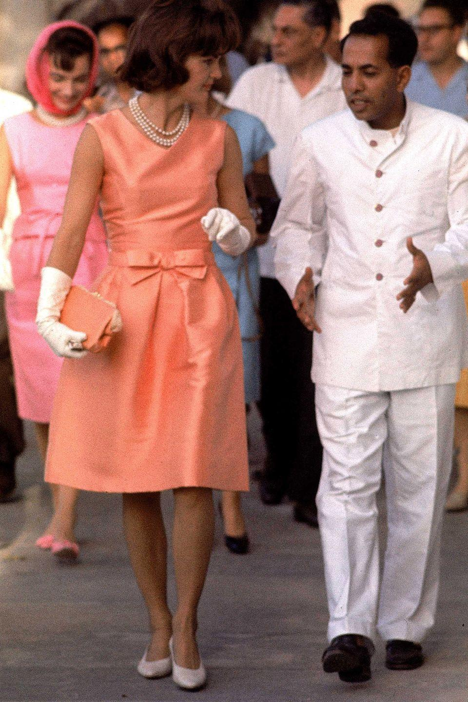 <p>For her state visit to India in 1962, Kennedy embraced the country's love of vibrant color. This orange-hued dress with bow detail was one of her many rainbow-hued ensembles for the excusion.</p>