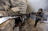 A female Syrian soldier from the Republican Guard commando battalion fires a machine gun during clashes with rebels in eastern Damascus on March 25, 2015 (AFP Photo/Joseph Eid)