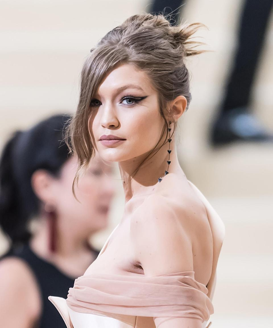 """<h3>2017</h3> <br><br>If anyone could get you to <a href=""""https://www.refinery29.com/en-us/2017/05/152586/met-gala-2017-drugstore-beauty"""" rel=""""nofollow noopener"""" target=""""_blank"""" data-ylk=""""slk:buy drugstore makeup"""" class=""""link rapid-noclick-resp"""">buy drugstore makeup</a>, it's Gigi at the Met Gala — which is exactly where she wore an $8 Maybelline eyeliner to create this dramatic cat-eye. (Hadid's the face of the brand.)<span class=""""copyright"""">Photo: Gilbert Carrasquillo/GC Images.</span><br><br>"""
