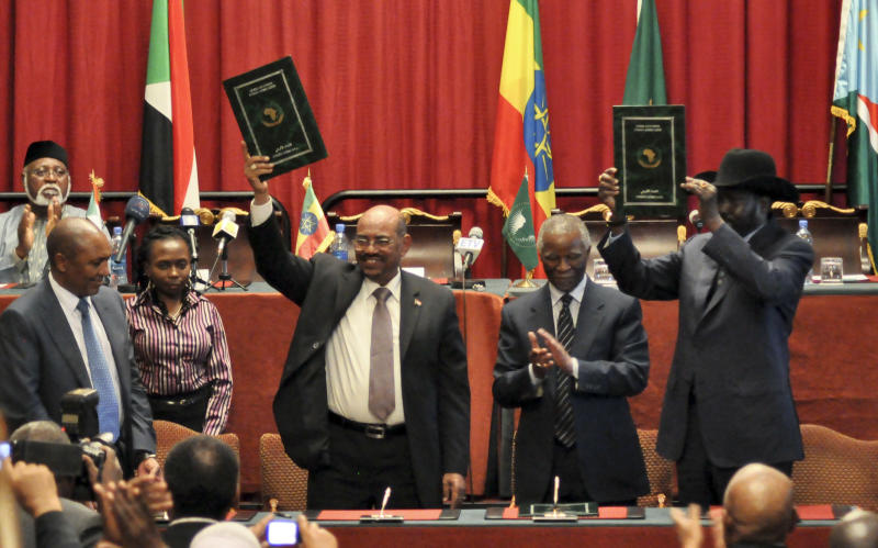 Sudan's President Omar al-Bashir, center-left, and South Sudan President Salva Kiir, right, gesture to celebrate the completion of a signing ceremony after the two countries reached a deal on economic and security agreements Thursday, Sept. 27, 2012 in Addis Ababa, Ethiopia. The presidents of Sudan and South Sudan signed agreements Thursday that will allow a resumption of oil exports from South Sudan, a demilitarized zone between their borders, and a cessation of all hostilities that brought the countries to the brink of all-out war just a few months ago. (AP Photo/Elias Asmare)