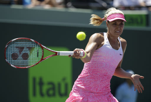 Sabine Lisicki, of Germany, hits a return to Serena Williams during their quarterfinal match at the Miami Open tennis tournament, Wednesday, April 1, 2015, in Key Biscayne, Fla. (AP Photo/Lynne Sladky)