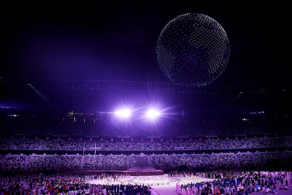 """<p>In a stunning spectacle, 1,824 drones form planet Earth in the sky above the stadium, as a junior chorus sings John Lennon's """"Imagine."""" It was very moving. Then there's a video shown of artists around the world singing along, including American singers <a href=""""http://www.popsugar.com/John-Legend"""" class=""""link rapid-noclick-resp"""" rel=""""nofollow noopener"""" target=""""_blank"""" data-ylk=""""slk:John Legend"""">John Legend</a> and <a href=""""http://www.popsugar.com/Keith-Urban"""" class=""""link rapid-noclick-resp"""" rel=""""nofollow noopener"""" target=""""_blank"""" data-ylk=""""slk:Keith Urban"""">Keith Urban</a>. </p>"""