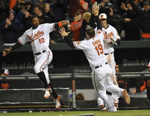 Baltimore Oriole's Chris Davis, center, is congratulated by Adam Jones, left, and Manny Machado after scoring the winning run against the Toronto Blue Jays in the ninth inning of a baseball game Monday, April 22, 2013 in Baltimore. Davis scored on a single by Nick Markakis. The Orioles won 2-1.(AP Photo/Gail Burton)