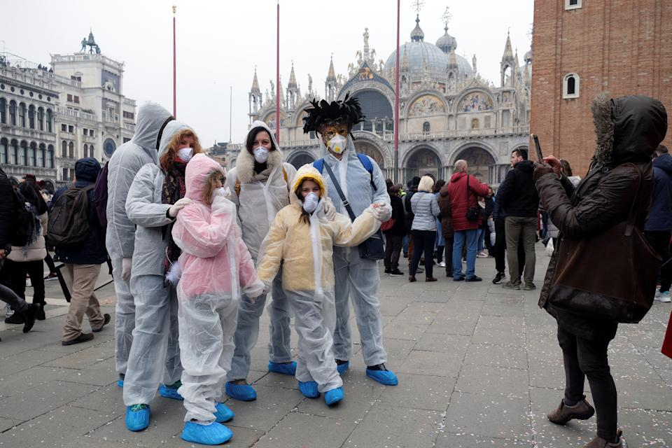 Carnival revellers wear protective face masks at Venice Carnival, where the last two days of the event as well as Sunday night's festivities, have been cancelled because of an outbreak of coronavirus in northern Italy. REUTERS/Manuel Silvestri