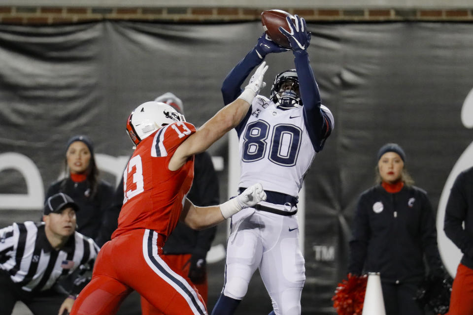 Cincinnati linebacker Ty Van Fossen (13) breaks up a pass in the end zone intended for Connecticut wide receiver Heron Maurisseau (80) during the second half of an NCAA college football game, Saturday, Nov. 9, 2019, in Cincinnati. (AP Photo/John Minchillo)