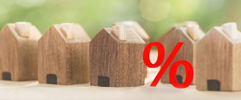 Small wooden houses with red percent sign, symbolizing mortgage rates