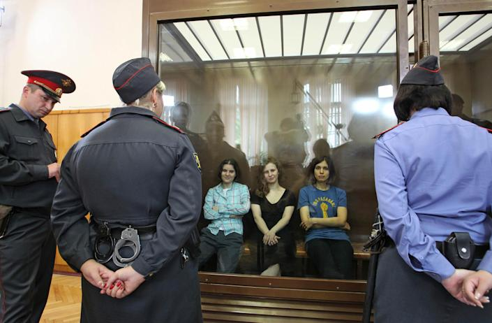 """Feminist punk group Pussy Riot members, from left, Yekaterina Samutsevich, Maria Alekhina and Nadezhda Tolokonnikova sit in a glass cage at a court room in Moscow, Russia on Friday, Aug 17, 2012. The women, two of whom have young children, are charged with hooliganism connected to religious hatred but the case is widely seen as a warning that authorities will only tolerate opposition under tightly controlled conditions. T-shirt on right worn by Tolokonnikova is Spanish and translates to """"They shall not pass"""", a slogan often used to express determination to defend a position against an enemy. (AP Photo/Mikhail Metzel)"""