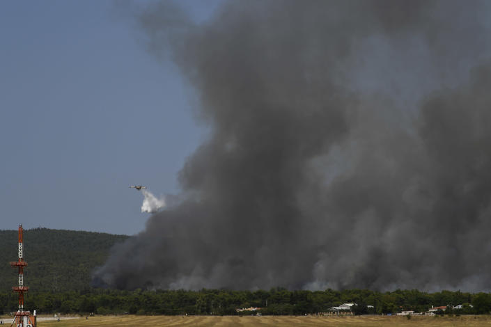 An airplane drops water during a wildfire that broke out in Tatoi, northern Athens, Greece, Tuesday, Aug. 3, 2021. The Greek Fire Service maintained an alert for most of the country Tuesday and Wednesday, while public and some private services shifted operating hours to allow for afternoon closures. (AP Photo/Michael Varaklas)