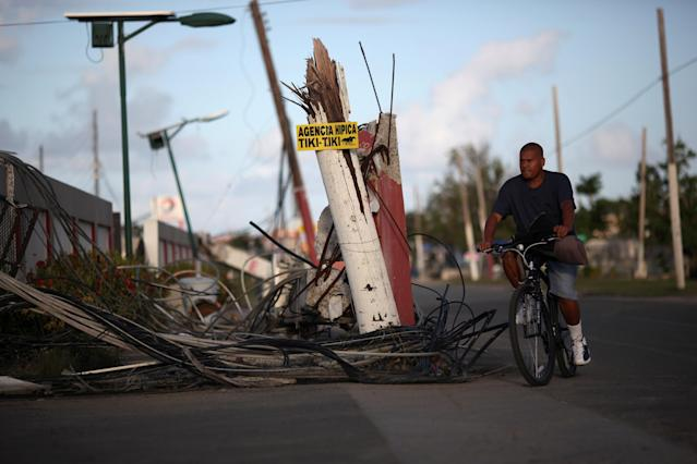 "A man rides a bicycle past downed cables and a partially collapsed utility pole, after Hurricane Maria hit the island in September, in Humacao, Puerto Rico January 25, 2018. The sign reads: ""Equestrian agency Tiki-Tiki.""REUTERS/Alvin Baez"