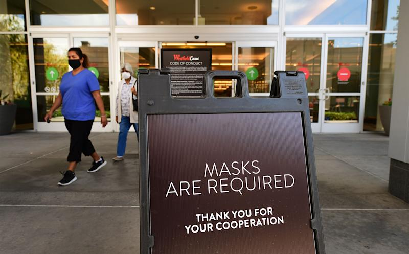 Women wearing facemasks exit a shopping mall where a sign is posted at an entrance reminding people of the mask requirement Westfield Santa Anita shopping mall on June 12, 2020 in Arcadia, California, as