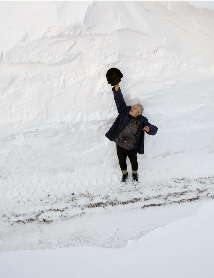 Nicolae Cocioaba, 58, raises his hand holding his hat to show the height of snow on the road in the village of Silistea Glodeanu, Romania, Tuesday, Feb. 14, 2012 the day after more snow storms hit the area.Snow as deep as 15 feet (4.5 meters) isolated areas of Romania, Moldova and Albania on Tuesday, and helicopters and army trucks were used to deliver food and medicine, and to transport sick people to hospitals.(AP Photo/Vadim Ghirda)