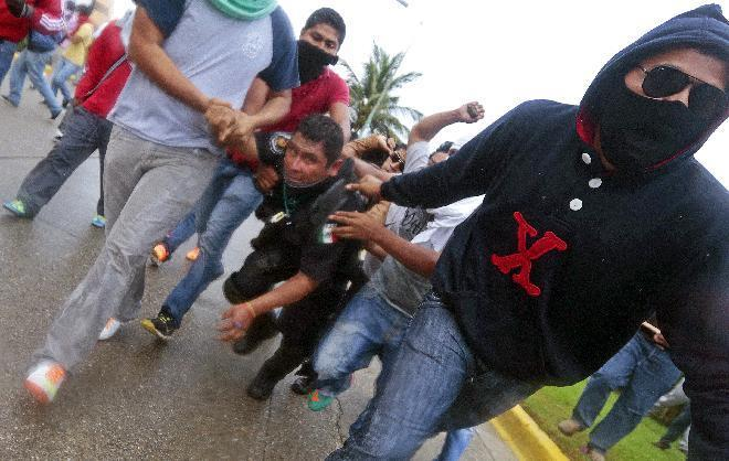 Demonstrators hold a riot policeman following a protest against the massacre of 43 students, near the airport in Acapulco, in Mexico's Guerrero State, on November 10, 2014 (AFP Photo/Pedro Pardo)