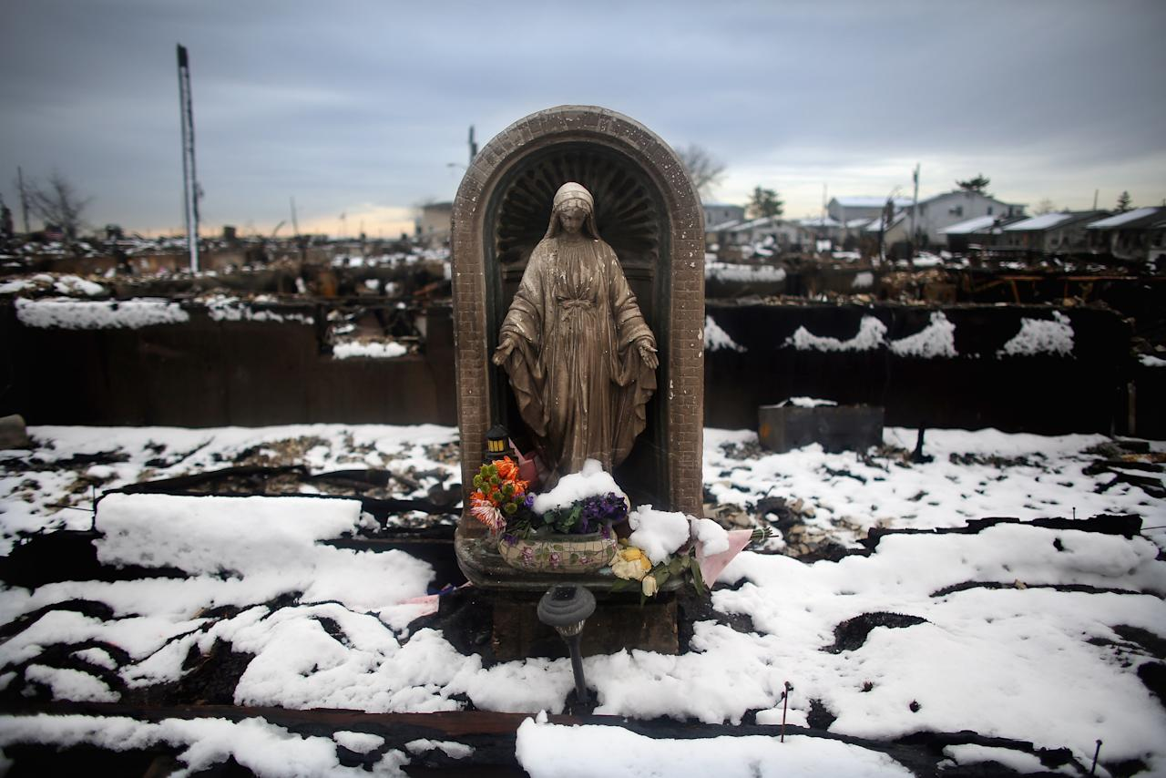 NEW YORK, NY - NOVEMBER 08:  Snow from a Nor'Easter storm coats homes burned in the aftermath of Superstorm Sandy amid a statue of the Virgin Mary on November 8, 2012 in the Breezy Point neighborhood of the Queens borough of New York City. The storm brought gusting winds, rain, and snow and forced the cancelation of flights for thousands of passengers flying into and out of JFK, LaGuardia and Newark.  (Photo by Mario Tama/Getty Images)