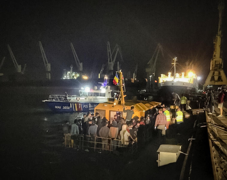 In this image provided by the Romanian border police, a ship carrying migrants docks in the Black Sea port of Constanta, Romania, early Wednesday, Sept. 13, 2017. Romania's coast guard has rescued before dawn more than 150 migrants from Iraq and Iran, of which were 53 children, from a ship in distress on the Black Sea, on what is becoming a new route for migrants trying to reach Western Europe. (Politia de Frontiera Romana via AP)