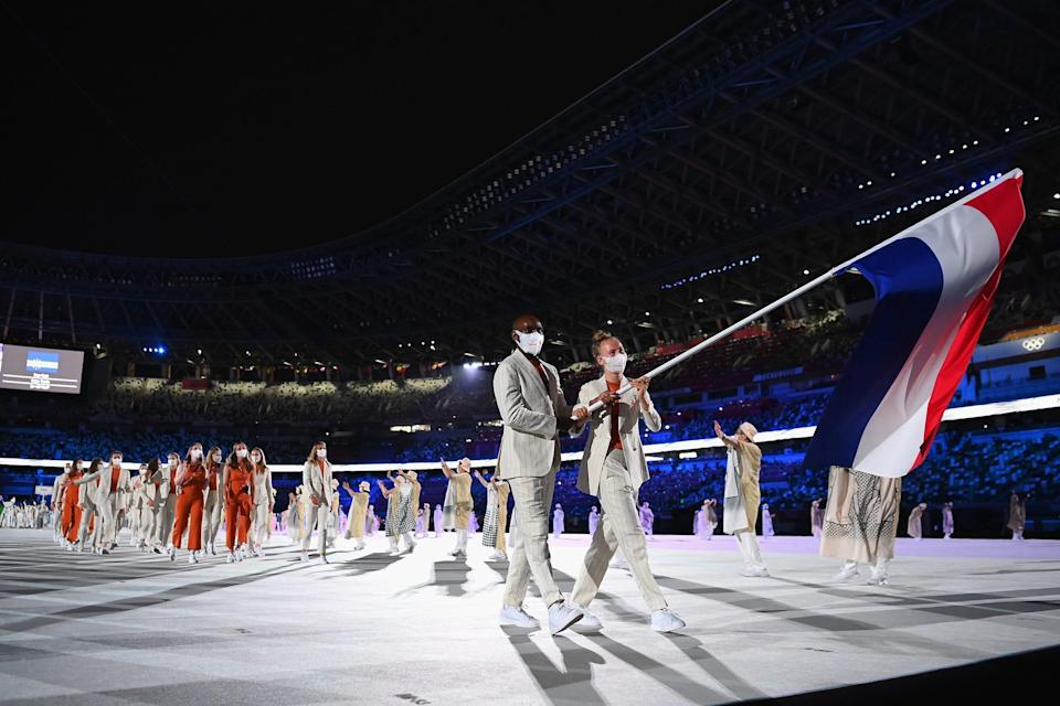 Flag bearers Keet Oldenbeuving and Churandy Martina of Team Netherlands lead their team out during the opening ceremony.
