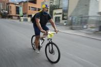 Andres Burgos, a 55-year-old publicist, rides his bicycle carrying a backpack filled with arepas or corn flour patties, in Caracas, Venezuela, Wednesday, Oct. 21, 2020. Five days a week, he rises before dawn to make the popular Venezuelan corn flour patties known as arepas at home. Then, he sets out on his bike to distribute them to people around Caracas from his backpack. (AP Photo/Ariana Cubillos)