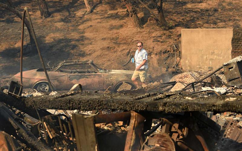 Eyad Jarjour (L) views his neighbor's burned residence after flames from the Saddleridge Fire tore through the region in Granada Hills, California on October 11, 2019. | JOSH EDELSON/Getty Images