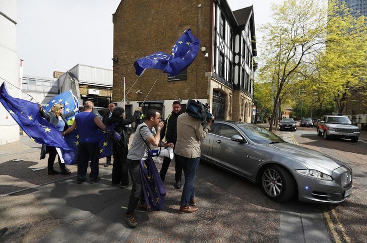 Pro-European Union demonstrators wave flags as Britain's Prime Minister Theresa May leaves ITV's studios, in London