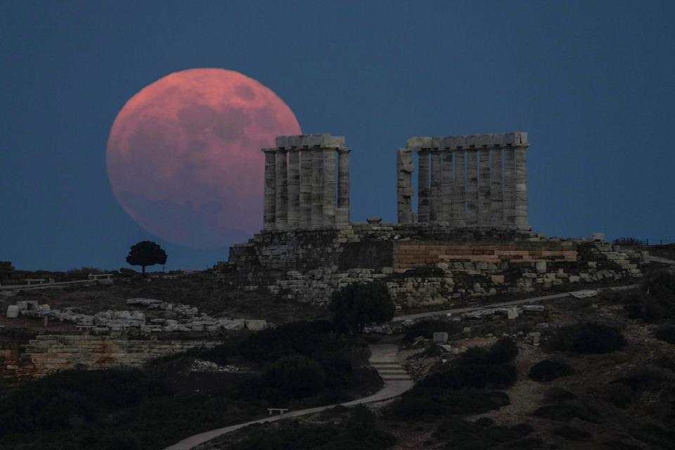 The strawberry full moon rises behind the ancient marble temple of Poseidon at Cape Sounion, about 45 miles south of Athens, on Thursday, June 24, 2021.
