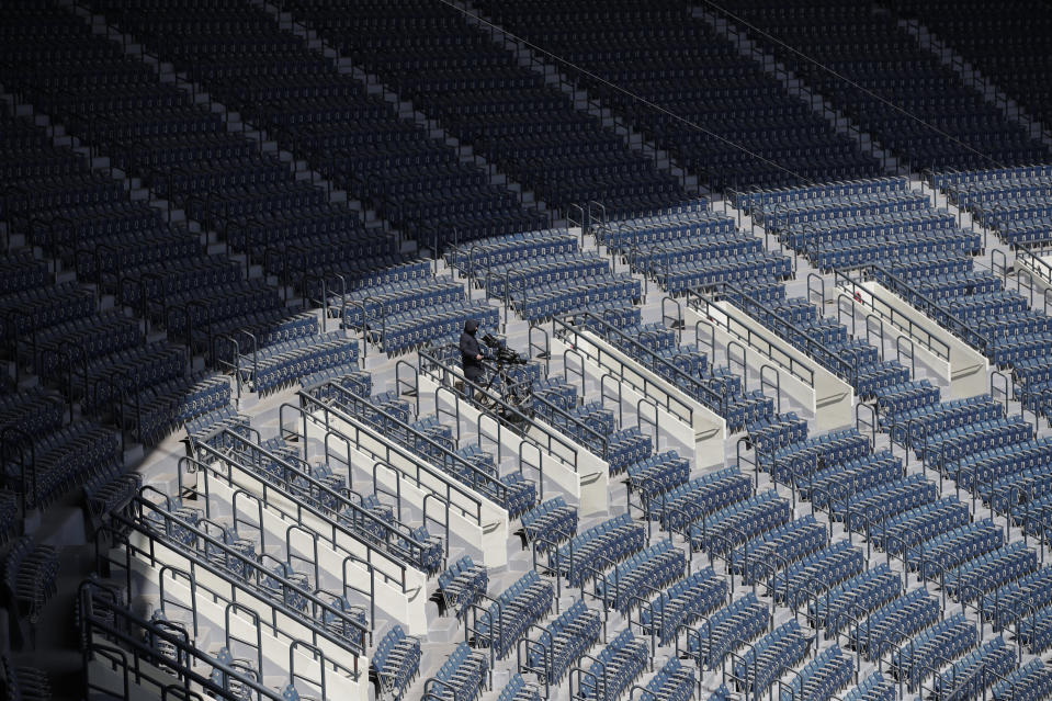 FILE - In this April 21, 2020, file photo, a TV cameraman works in rows of empty seats during a preseason baseball game between Doosan Bears and LG Twins in Seoul, South Korea. (AP Photo/Lee Jin-man, File)