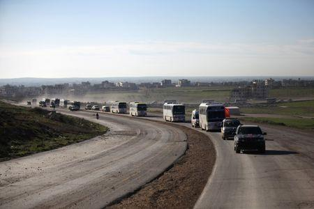 Buses carrying rebel fighters and their families who evacuated the besieged Waer district arrive on the southern outskirts of the Syrian city of al-Bab