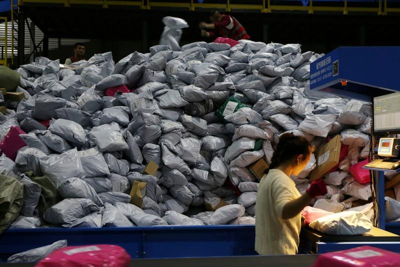 Employees sort parcels at a logistics base on the Singles' Day online shopping festival in Yiwu