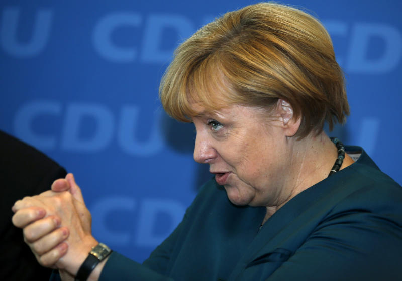 German Chancellor and chairwoman of the German Christian Democratic party,CDU, Angela Merkel, gestures as she arrives for a party's board meeting in Berlin, Monday, Sept. 23, 2013. Top party officials are meeting to talk strategy about reaching out to the center-left rivals they need to form a government, after Merkel won a stunning victory in Germany's elections on Sunday. (AP Photo/Michael Sohn)