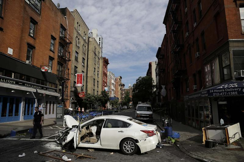A car damaged in an accident sits in the middle of the street in New York, Wednesday, June 19, 2013. Fire authorities say eight people have been hurt, several of them seriously, after the car jumped a curb and slammed into a Manhattan store. A witness said the driver lost control about a block away and plowed through everything on the sidewalk. (AP Photo/Seth Wenig)