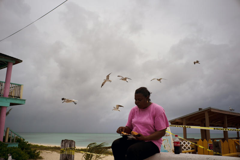 Seagulls fly near a woman feeding them chicken and french fries as dark clouds gather and Hurricane Dorian approaches, on Taino beach in Freeport, Grand Bahama, Bahamas, Sunday Sept. 1, 2019. (AP Photo/Ramon Espinosa)