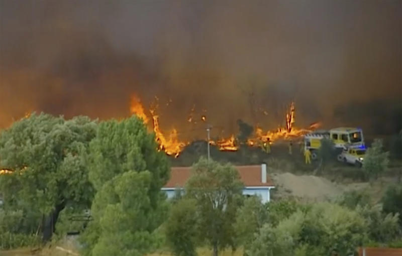 In this grab taken from video on Saturday, July 20, 2019 provided by TVI, members of the emergency services try to extinguish wildfires, in Vila de Rei, Portugal. Portuguese authorities say 1,000 firefighters are working to contain wildfires that have injured eight firefighters and one civilian. Portugal's Civil Protection Agency says Sunday that firefighters are combating flames that broke out Saturday across three fronts in the district of Castelo Branco, 200 kilometers (124 miles) northeast of Lisbon, the capital. This is the first major wildfire in Portugal this year. (TVI via AP)
