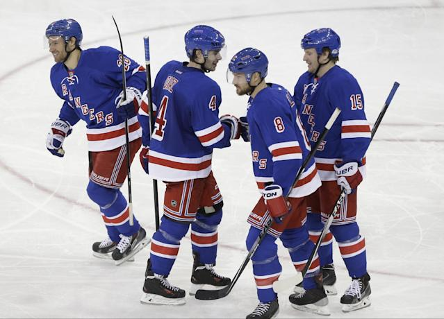 New York Rangers' Dominic Moore (28) smiles after his goal against the Philadelphia Flyers, while teammates Raphael Diaz (4), Kevin Klein (8) and Derek Dorsett (15) congratulate one another during the third period of an NHL hockey game Wednesday, March 26, 2014 in New York. The Rangers won 3-1. (AP Photo/Frank Franklin II)