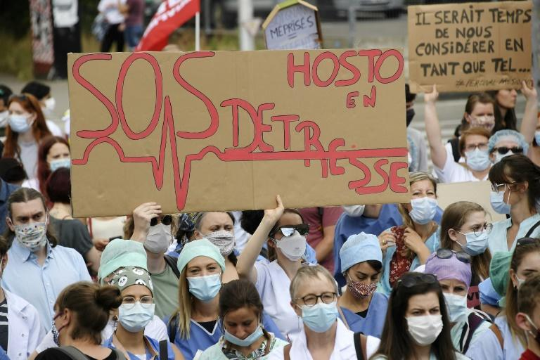 """Health workers, one holding a placard reading """"SOS Hospitals"""", take part in a demonstration to demand better working conditions in Strasbourg, eastern France"""