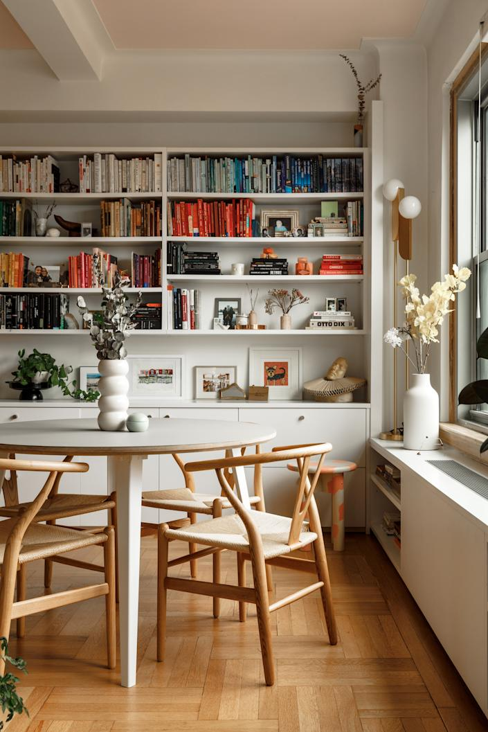 """<div class=""""caption""""> The dining area's <a href=""""https://www.architecturaldigest.com/story/cost-effective-built-ins-starrett-ringbom?mbid=synd_yahoo_rss"""" rel=""""nofollow noopener"""" target=""""_blank"""" data-ylk=""""slk:built-in bookshelves"""" class=""""link rapid-noclick-resp"""">built-in bookshelves</a> hold photographs, mementos, and a tidy array of rainbow-colored titles. </div>"""