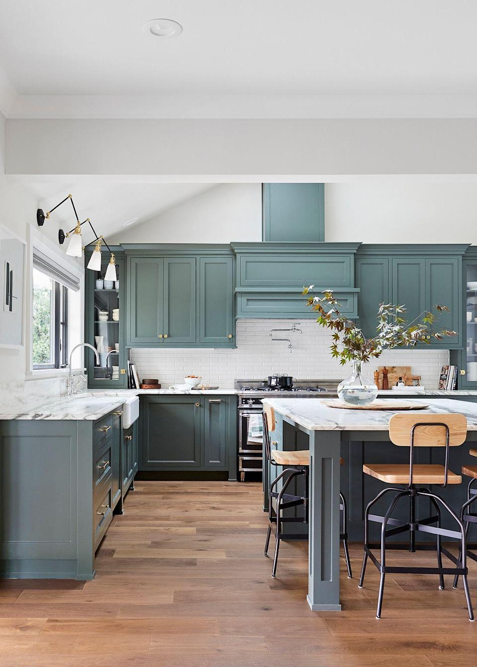 "Henderson tells us the house called for something that was ""original and special,"" and she wanted this kitchen to be the centerpiece of the home. ""Everyone always seems to gather in their kitchen, and this was open to both the family and dining rooms, so my goal was to create a mix of classic and modern, happy and sophisticated, with some moments,"" she says. Henderson also wanted to bring in a new big window to bring in a lot of natural light, but it is also a central view for anyone looking through it to see the kids playing in the yard below."
