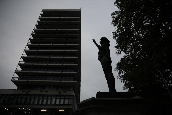 """A new black resin and steel statue entitled """"A Surge of Power (Jen Reid) 2020"""" by artist Marc Quinn stands after the statue was put up in the morning on the empty plinth of the toppled statue of 17th century slave trader Edward Colston, which was pulled down during a Black Lives Matter protest in Bristol, England, Wednesday, July 15, 2020. On June 7, anti-racism demonstrators pulled the 18-foot (5.5-meter) bronze likeness of Colston down, dragged it to the nearby harbor and dumped it in the River Avon, sparking both delight and dismay in Britain and beyond. (AP Photo/Matt Dunham)"""
