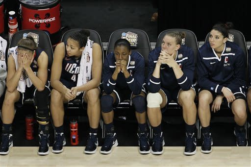 Connecticut players watch action at the end of overtime in the NCAA women's Final Four semifinal college basketball game against Notre Dame, in Denver, Sunday, April 1, 2012. Notre Dame won 83-75. (AP Photo/David Zalubowski)
