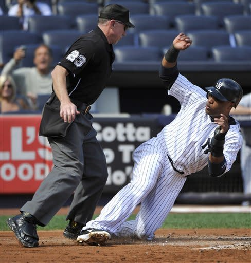 New York Yankees' Robinson Cano, right, almost slides into home plate umpire Lance Barksdale, left, as he scores on a sacrifice fly by Curtis Granderson during the first inning of the first baseball game of a day-night doubleheader against the Toronto Blue Jays Wednesday, Sept. 19, 2012, at Yankee Stadium in New York. (AP Photo/Bill Kostroun)