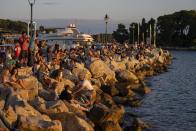 Holidaymakers enjoy sunset on the seafront in the Adriatic town of Rovinj, Croatia, Friday, Aug. 27, 2021. Summer tourism has exceeded even the most optimistic expectations in Croatia this year. Beaches along the country's Adriatic Sea coastline are swarming with people. Guided tours are fully booked, restaurants are packed and sailboats were chartered well in advance. (AP Photo/Darko Bandic)