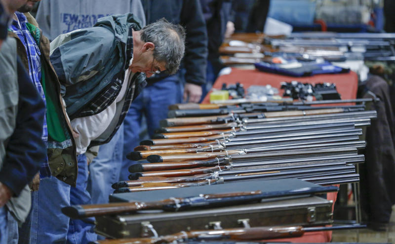 "FILE - In this Jan. 26, 2013 file photo, a customer looks over shotguns on display at the annual New York State Arms Collectors Association Albany Gun Show at the Empire State Plaza Convention Center in Albany, N.Y. A bipartisan quartet of senators, including two National Rifle Association members and two with ""F"" ratings from the potent firearms lobby, are quietly trying to reach compromise on expanding the requirement for gun-sale background checks. (AP Photo/Philip Kamrass, File)"