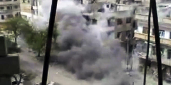 In this image made from amateur video released by the Shaam News Network and accessed Sunday, April 15, 2012, smoke rises from buildings following purported shelling in Homs, Syria. Syrian troops are reported to have shelled residential neighborhoods dominated by rebels in the central city of Homs Sunday, activists said, killing at least three people hours before the first batch of United Nations observers were to arrive in Damascus to shore up a shaky truce. (AP Photo/Shaam News Network via AP video) TV OUT, THE ASSOCIATED PRESS CANNOT INDEPENDENTLY VERIFY THE CONTENT, DATE, LOCATION OR AUTHENTICITY OF THIS MATERIAL