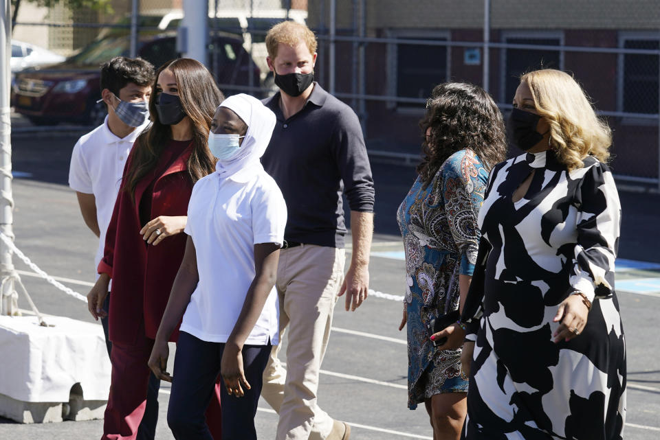Prince Harry and Meghan, the Duke and Duchess of Sussex, are accompanied by students and Principal Melitina Hernandez, second from right, and New York City School Chancellor Meisha Porter, right, during their visit to P.S. 123, the Mahalia Jackson School, in New York's Harlem neighborhood, Friday, Sept. 24, 2021. (AP Photo/Richard Drew)